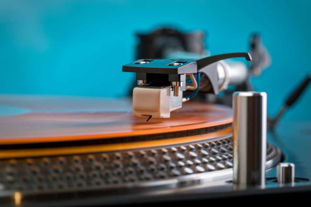 tonearm clear orange vinyl record turquoise background