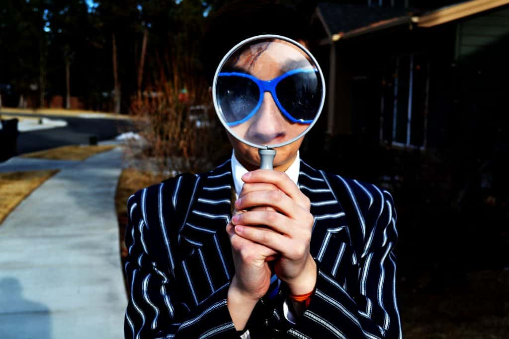 man with shaggy black hair in striped suit holding magnifying glass in front of face enlarging his blue sunglasses