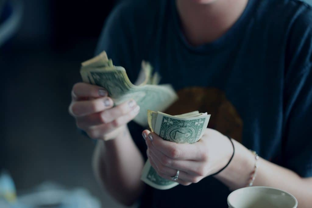 woman counting dollar bills