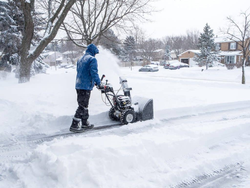 Man-Removing-Snow-with-a-Snowblower in a blue coat