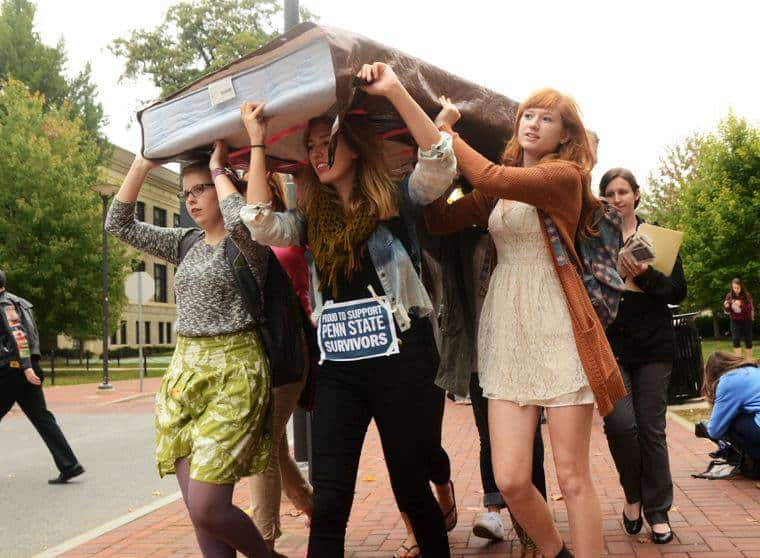 group of college girls carrying mattress down sidewalk on moving day