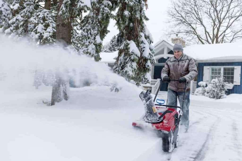 man running snowblower in front of blue house