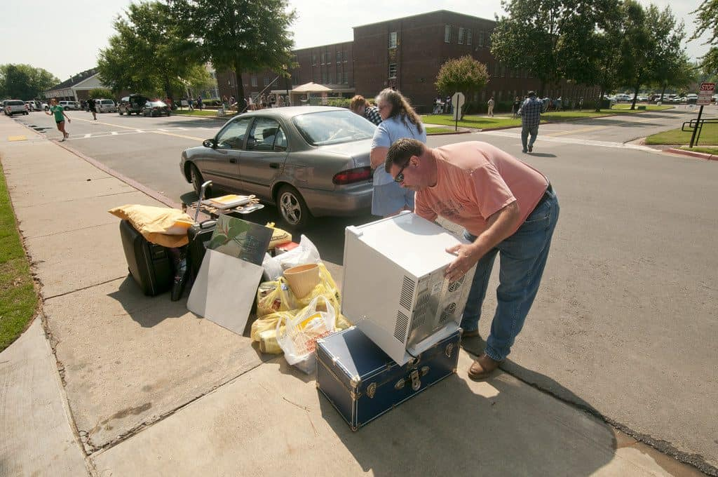 parents helping college student on moving day with lots of stuff on sidewalk
