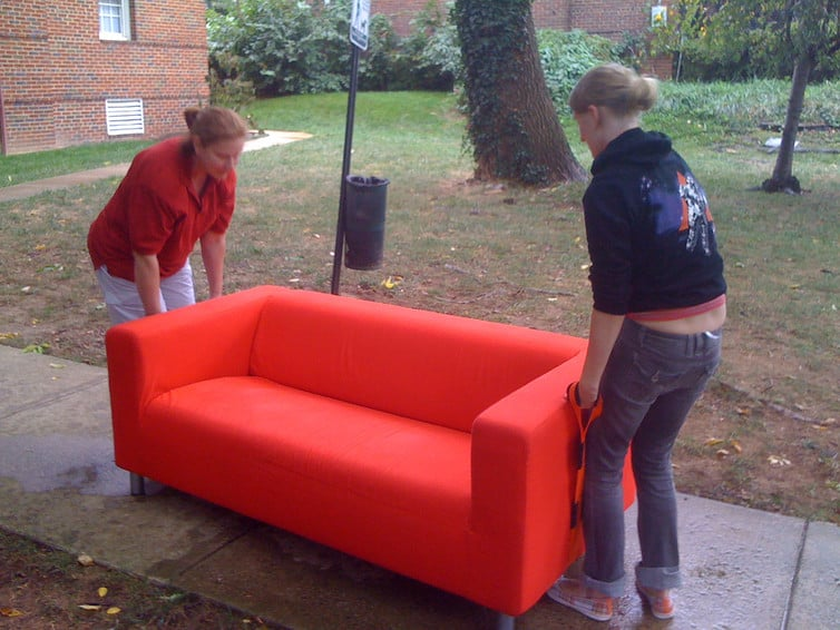 two college students girls moving small orange couch