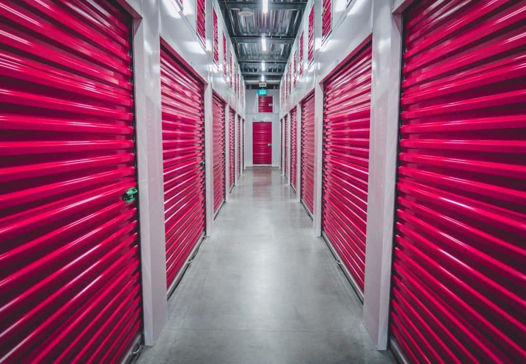 indoor self storage facility hallway with red storage unit doors