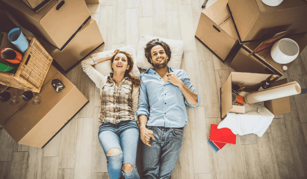 couple laying on floor surrounded by moving boxes moving to an apartment