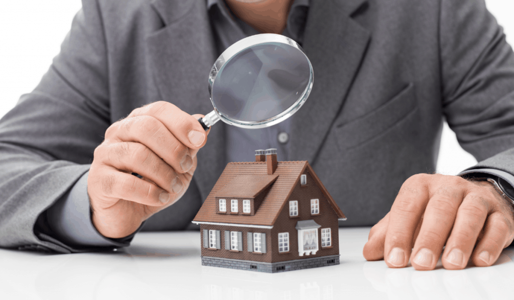 man in suit holding magnifying glass over toy house home inspection