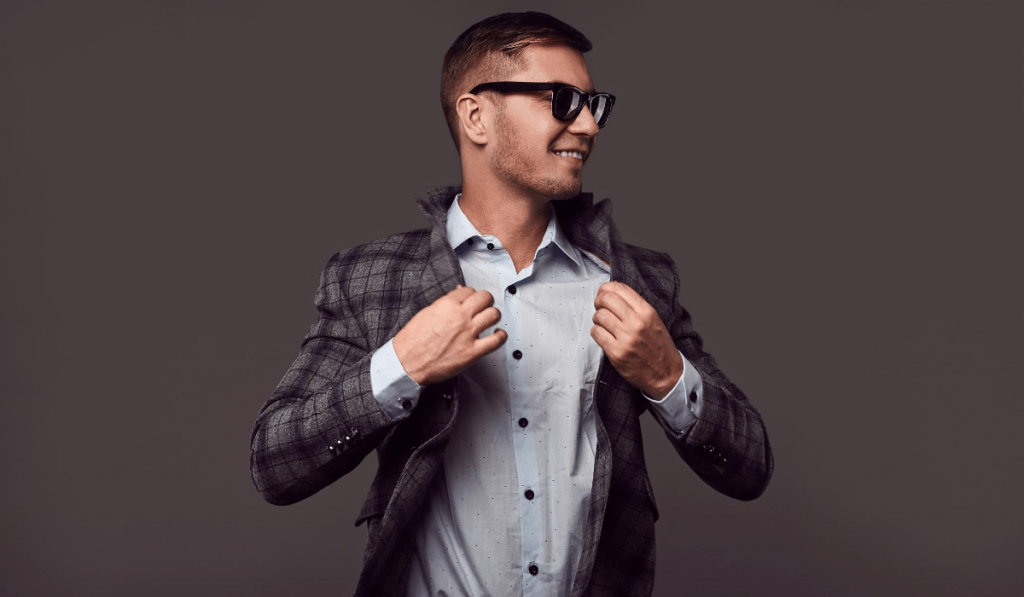 man with thick black glasses wearing a button down shirt and plaid blazer in front of black background