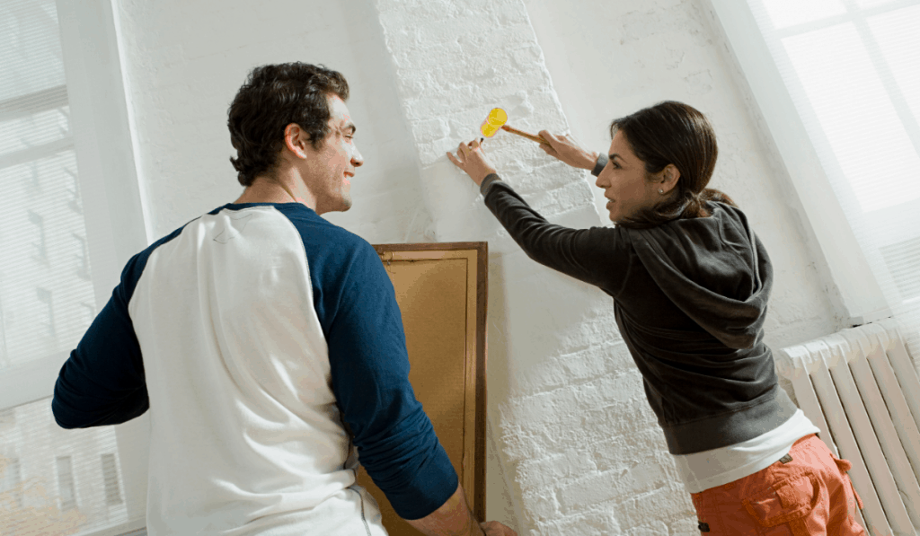 man woman couple hammering a nail to hang artwork on white brick wall