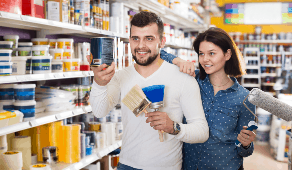 man woman couple in paint store holding brushes paint roller choosing paint colors