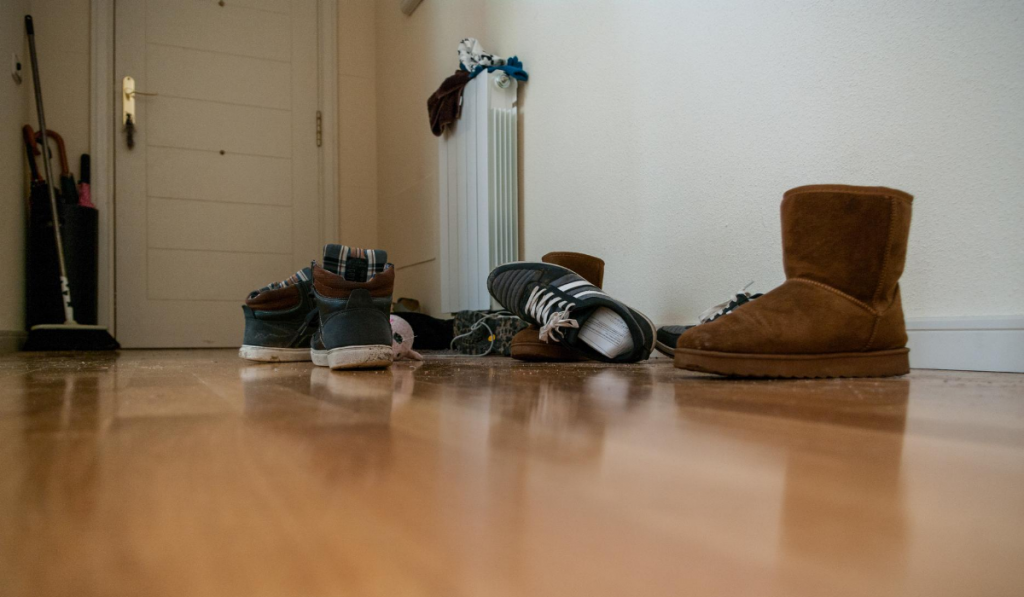 shoes-scattered-on-wooden-floor-near-entry-sneakers-ugg-boots