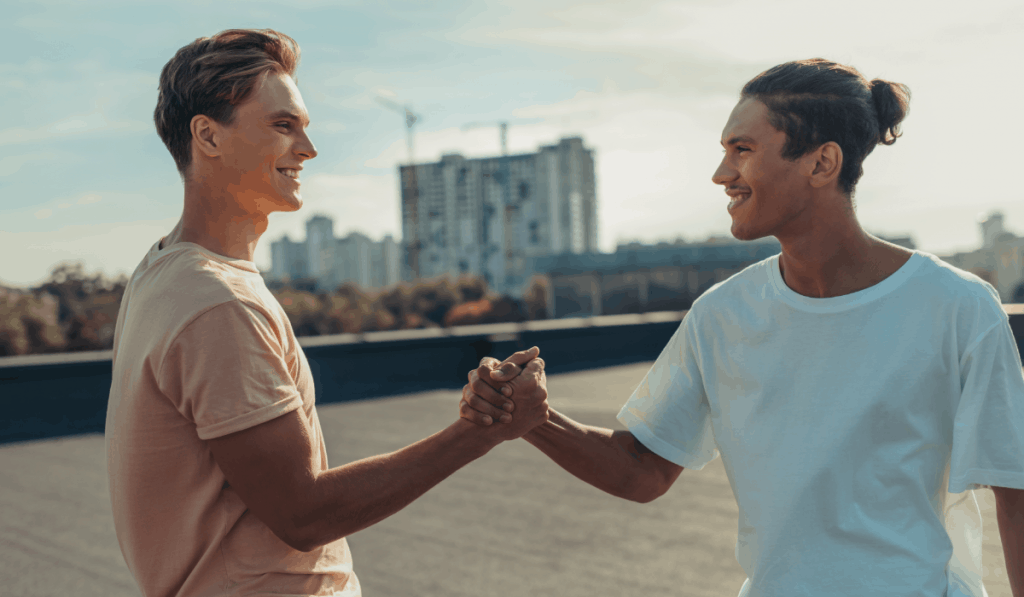 two men shaking hands grasping hands smiling on rooftop