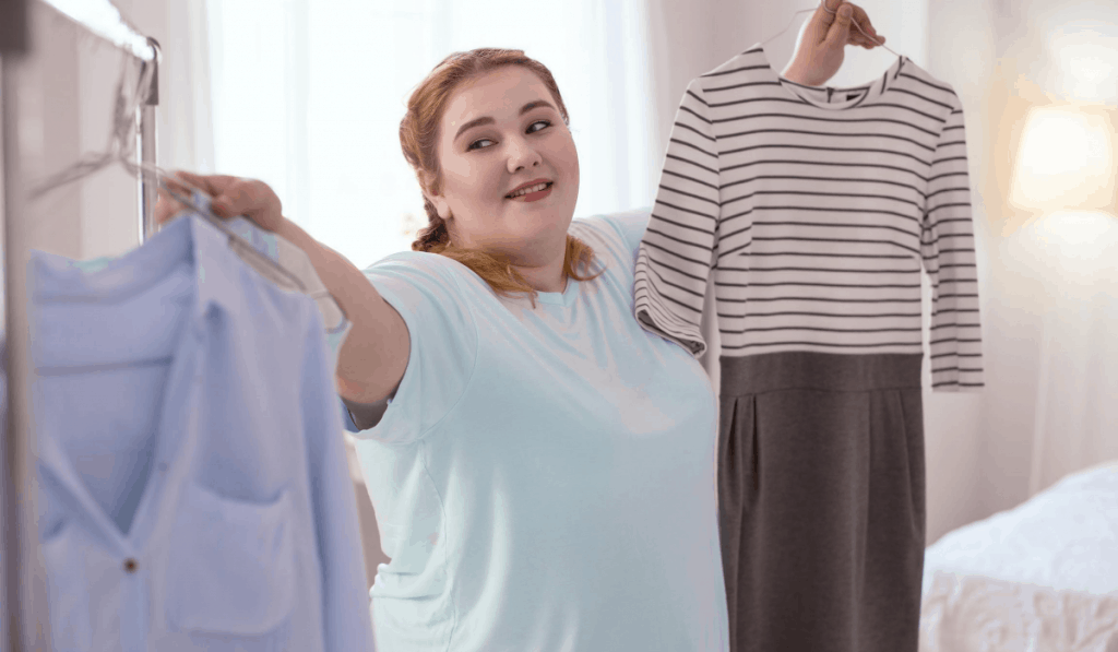 woman hanging shirt on garment rack choosing outfits