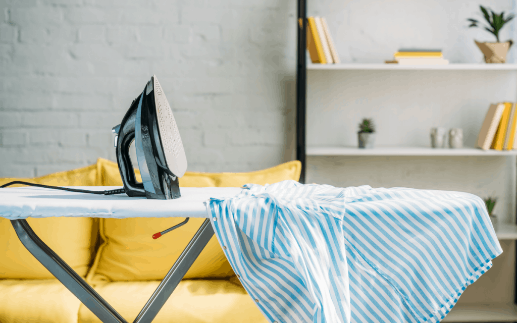 ironing board with iron and striped shirt in living room