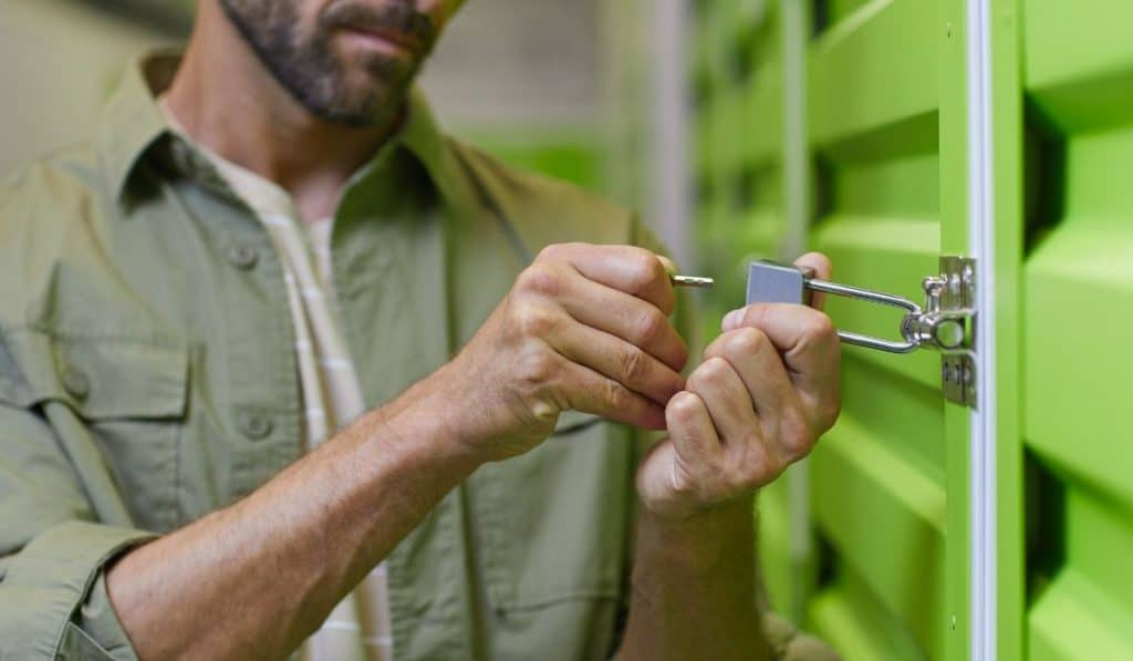 man opening the padlock of his storage unit