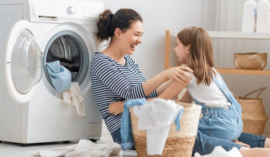 mom and daughter having fun while doing the laundry