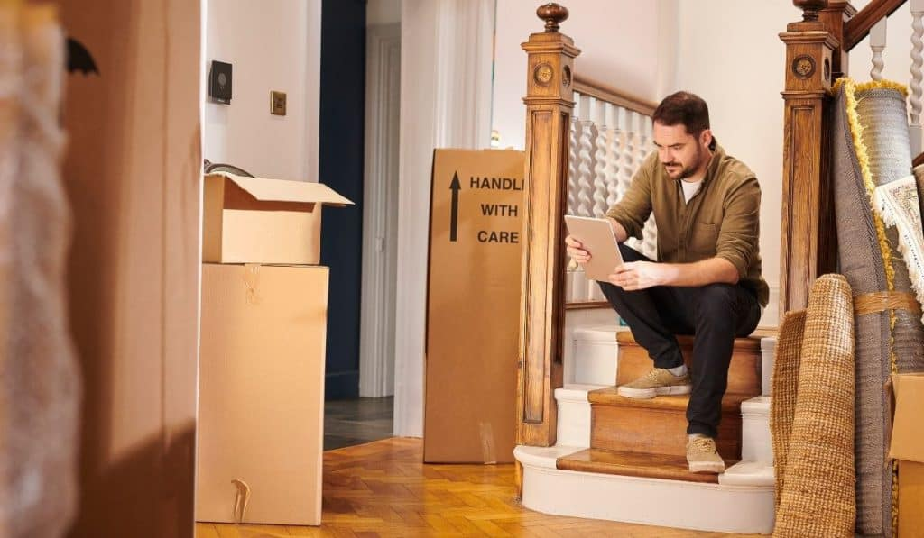 man moving out sitting on the stairs holding a table