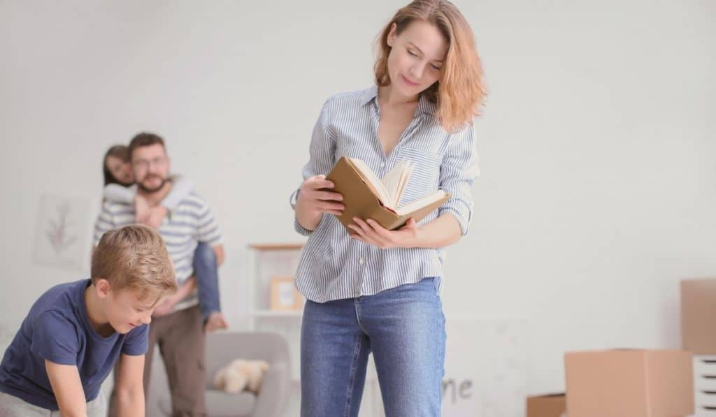 woman reading an old book of her deceased parent and her family with her helping with the packing of her parents things